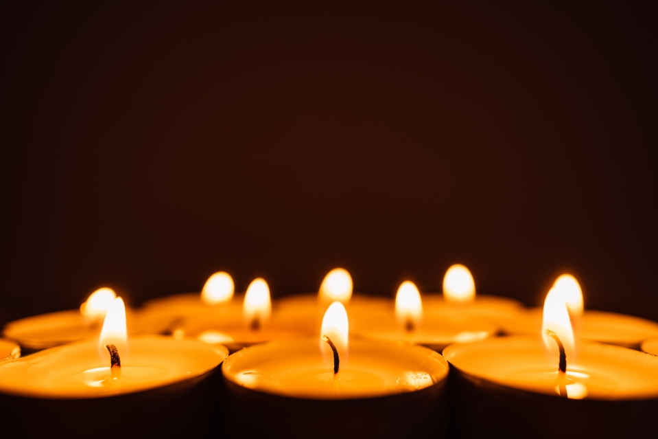 Burning candles in a row in the dark.